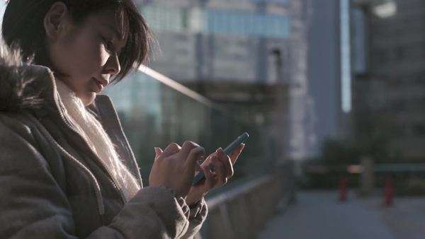 Slow-motion shot of a young Japanese woman using smartphone in Tokyo Royalty-free stock video