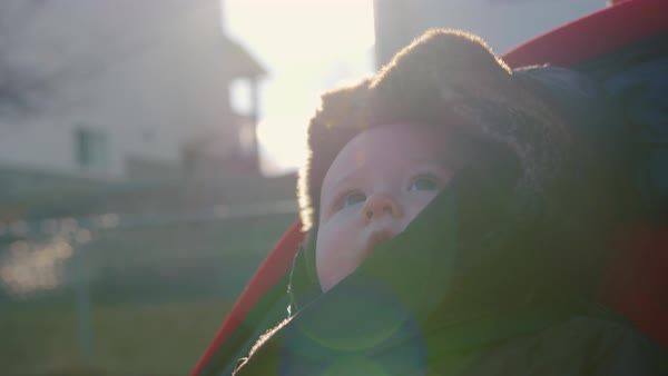 Baby girl going for a ride in a stroller with sunset behind her in slow motion Royalty-free stock video