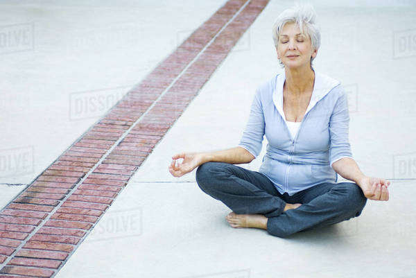 Senior woman sitting in lotus position, eyes closed Royalty-free stock photo