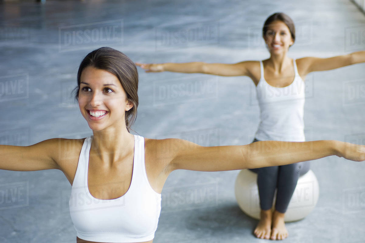Teenage twin sisters sitting on fitness balls, arms outstretched, both smiling Royalty-free stock photo