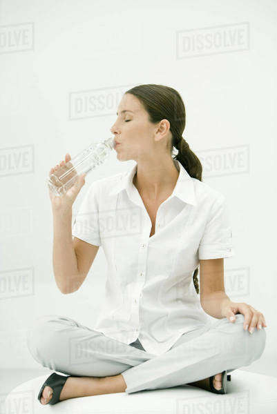 Woman sitting cross-legged, drinking water, eyes closed Royalty-free stock photo