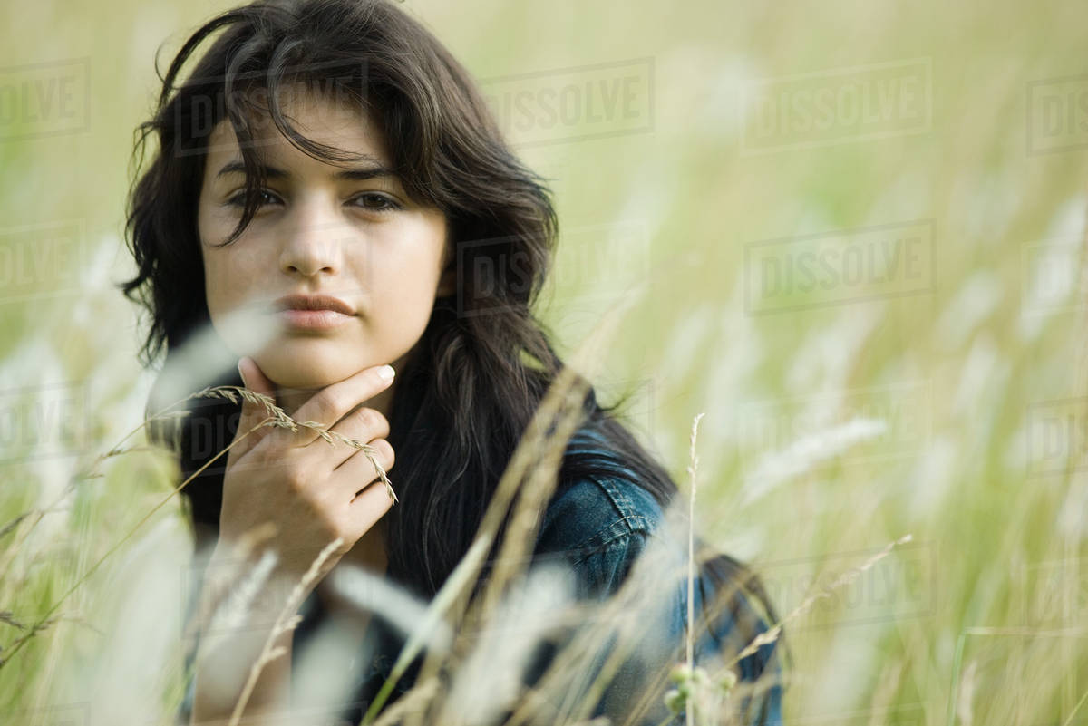 Young woman sitting in tall grass with hand under chin, looking at camera Royalty-free stock photo