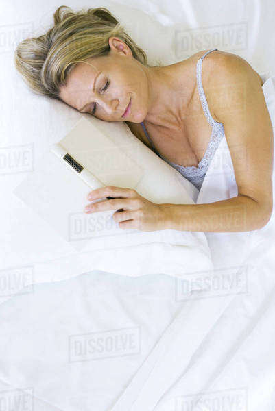 Woman asleep in bed with open book next to her Royalty-free stock photo