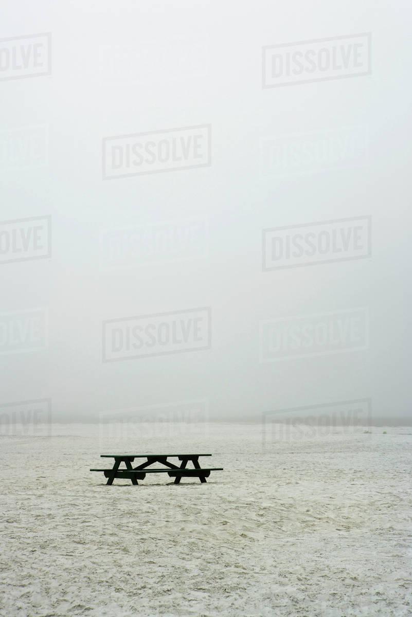 Picnic table on empty, foggy beach Royalty-free stock photo