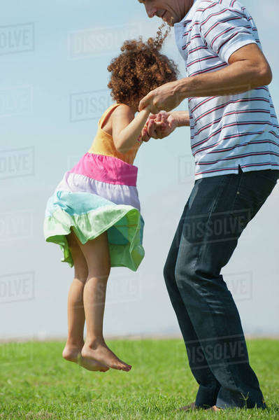 Father lifting daughter in air, side view Royalty-free stock photo
