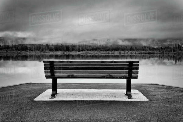 Black and white shot of empty bench facing Vermillion Lakes in Banff , Alberta, Canada. Royalty-free stock photo