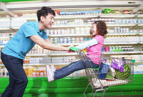Father Pushing Daughter in Shopping Cart Inside Supermarket, Laughing Royalty-free stock photo