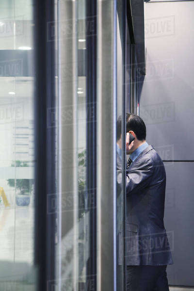 Businessman on the phone, glass wall Royalty-free stock photo