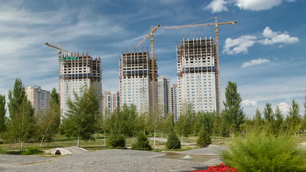 Overview of a large construction site timelapse with red flowers and green grass. Near new mosque and the Palace of Peace and Reconciliation in Astana Royalty-free stock video