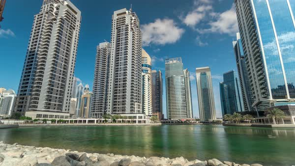 Residential buildings in Jumeirah Lake Towers reflected in water timelapse in Dubai, UAE. View with blue cloudy sky from stones near lake Royalty-free stock video