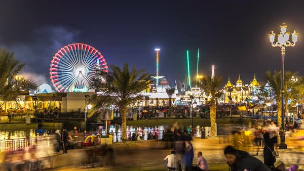 Main square and lake in Global Village with crowd and attractions timelapse in Dubai, UAE. Brightly colored lights and highly detailed pavilion facades have helped make Global Village one of Dubai's most popular attractions Royalty-free stock video