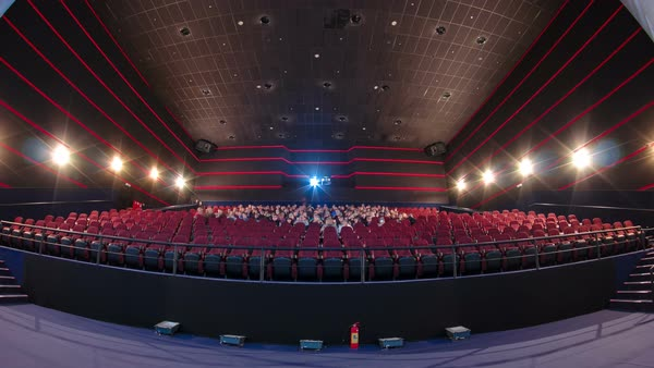 Viewers fill the cinema hall and watch motion picture at movie theatre timelapse. Red chairs and big screen Royalty-free stock video