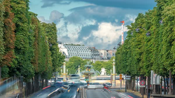 The beautiful Concorde Square in Paris timelapse - the famous fountain at obelisk called Fontaine des Fleuves. Traffic on road with green trees on the sides. PARIS, FRANCE Royalty-free stock video