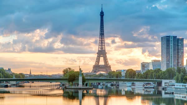 Eiffel Tower sunrise timelapse with boats on Seine river and in Paris, France. View from Mirabeau bridge. Modern buildings and The Statue of Liberty Royalty-free stock video