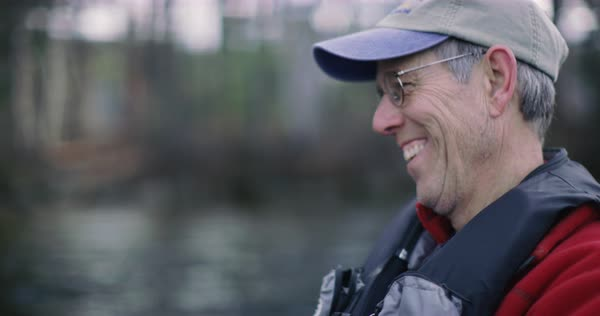 Hand-held shot of a man laughing by a river Royalty-free stock video