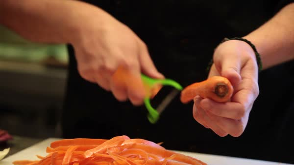 Hands cutting carrots. Person cutting veggies. Royalty-free stock video