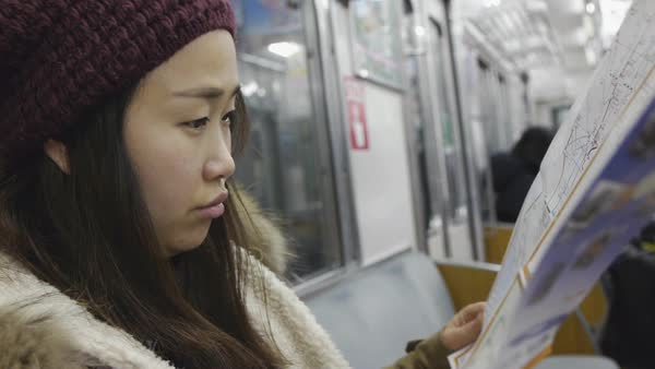 Hand-held shot of a woman reading a public transportation map in a subway train Royalty-free stock video