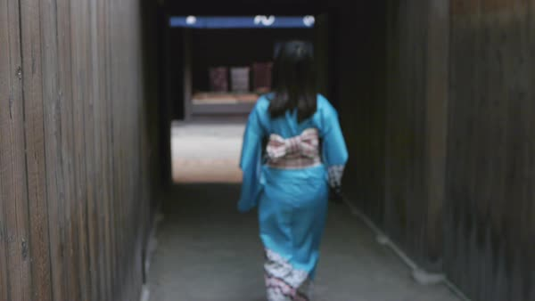 Hand-held shot of a woman in kimono walking away from camera Royalty-free stock video