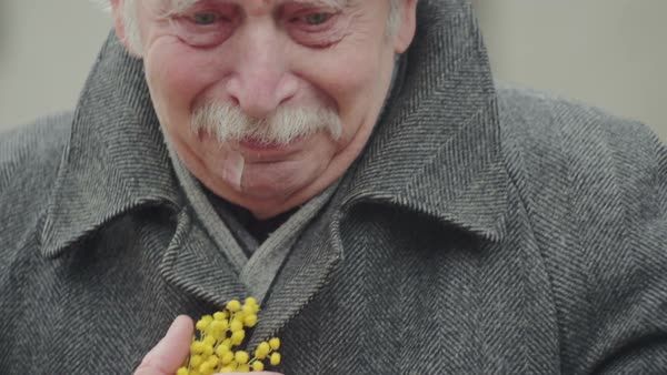 Senior crying in the street holding hands with flowers. Royalty-free stock video