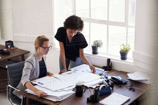 Two young businesswomen studying documents in an office Royalty-free stock photo