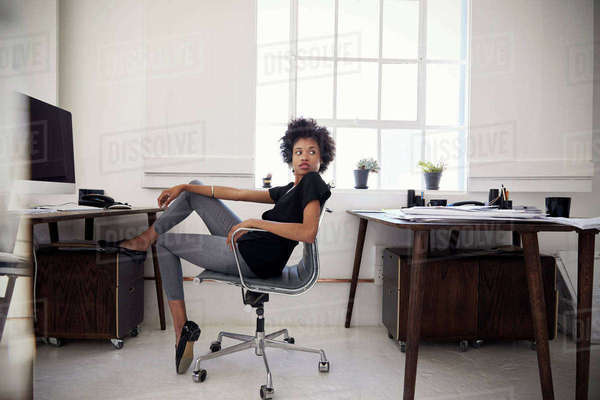 Young businesswoman sits in an office looking over shoulder Royalty-free stock photo