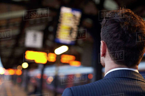 Businessman stands on platform waiting for train to arrive Royalty-free stock photo