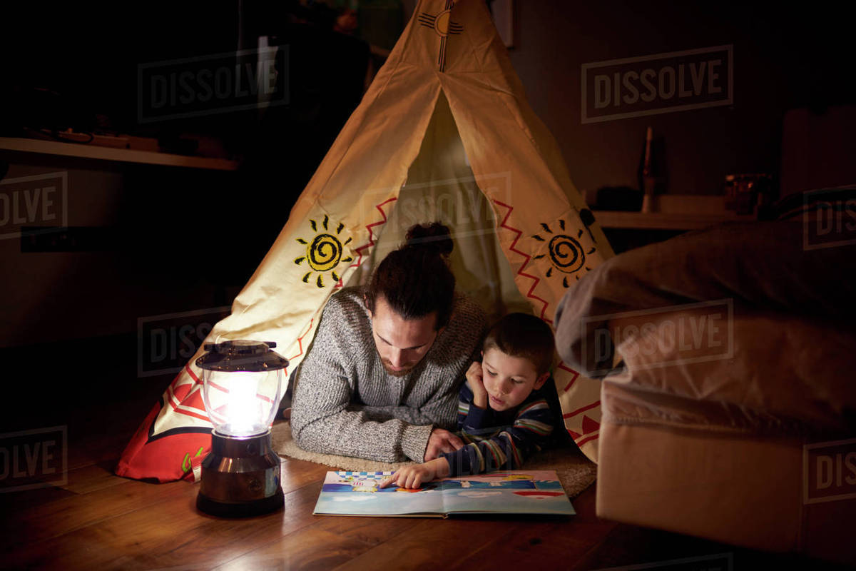 Father and son reading inside tent set up indoors stock photo