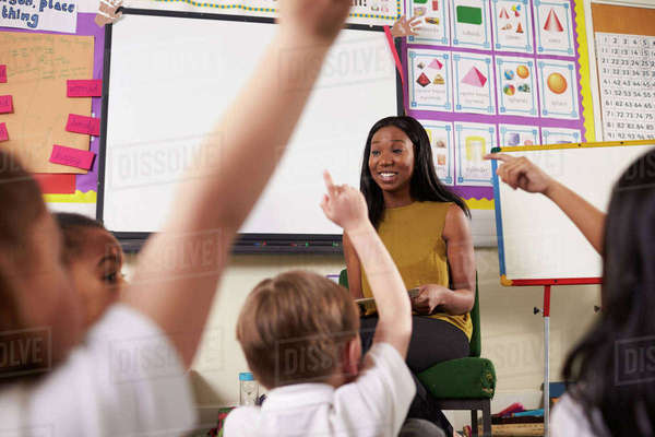 Teacher asks elementary school pupils question in classroom Royalty-free stock photo