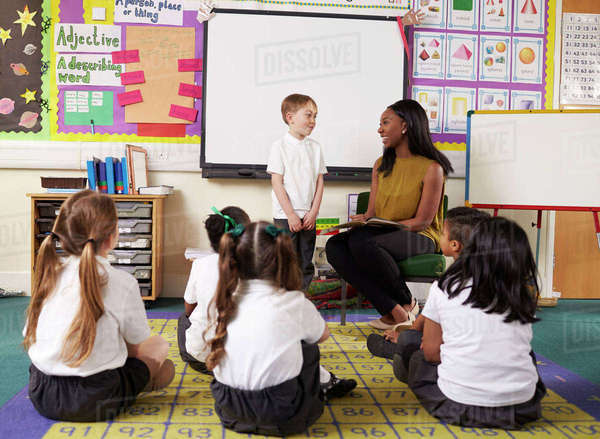 Male elementary pupil reading in front of class Royalty-free stock photo