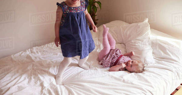Daughters playing game on parent's bed Royalty-free stock photo