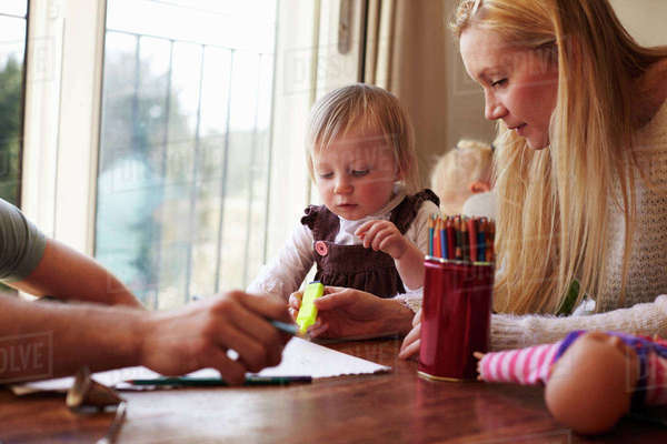 Family sitting at table and drawing pictures together Royalty-free stock photo