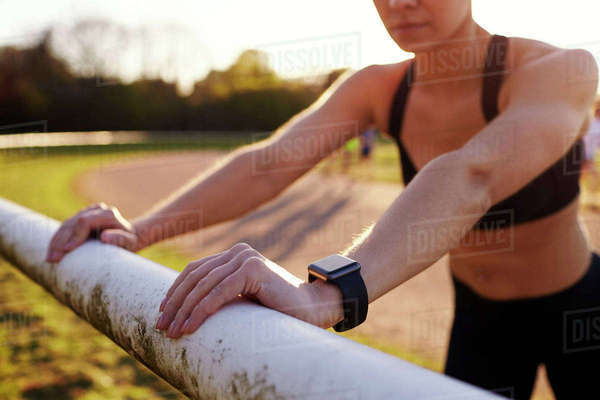 Young Woman Wearing Activity Tracker Stretches Before Run Royalty-free stock photo