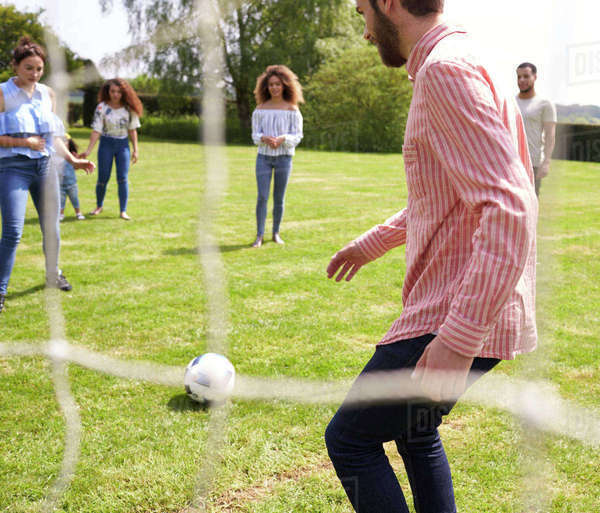 Friends have fun playing with a football on a playing field Royalty-free stock photo