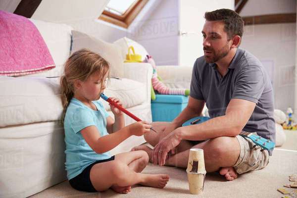 Father Watches Daughter Playing Whistle In Playroom Royalty-free stock photo