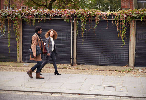Stylish Young Couple Walking Past Garages On City Street Royalty-free stock photo