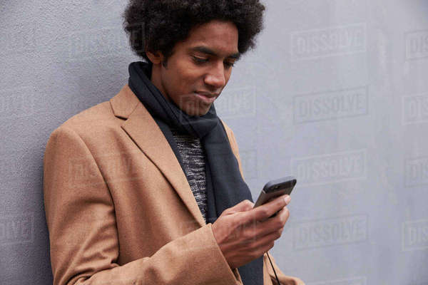 Man Leaning Against Wall Using Mobile Phone On City Street Royalty-free stock photo