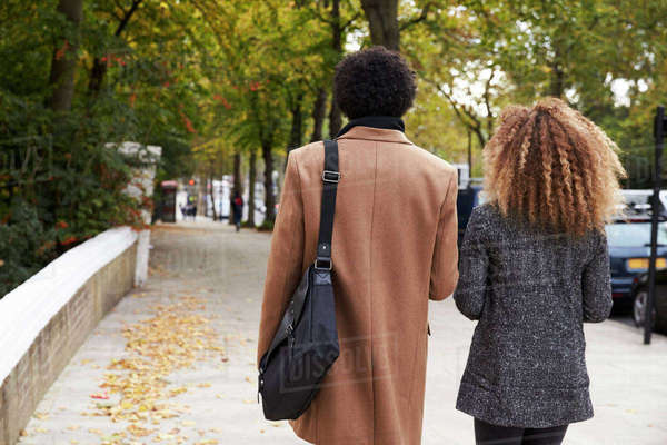 Rear View Of Stylish Couple Walking On Fall Street In City Royalty-free stock photo
