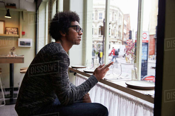 Young Man Using Mobile Phone To Update Social Media In Cafe Royalty-free stock photo
