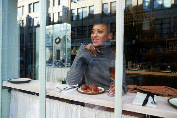 Young woman sitting in cafe with food, seen through window Royalty-free stock photo
