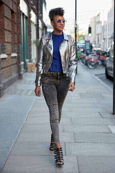 Woman wearing silver jacket and sunglasses walking in street Royalty-free stock photo