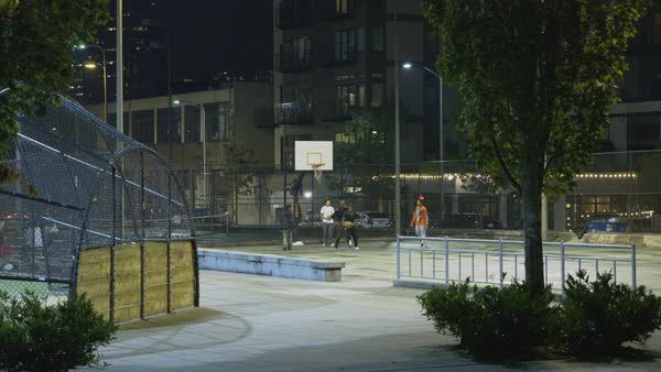 Static shot of young men playing basketball in a park Rights-managed stock video