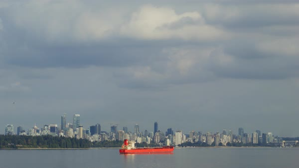 Establishing shot of a red cargo ship sailing in Vancouver, Canada Rights-managed stock video