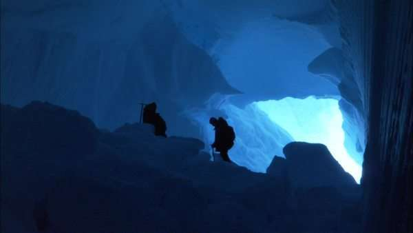 Zooming out shot of people climbing up crevasse in Antarctica Rights-managed stock video