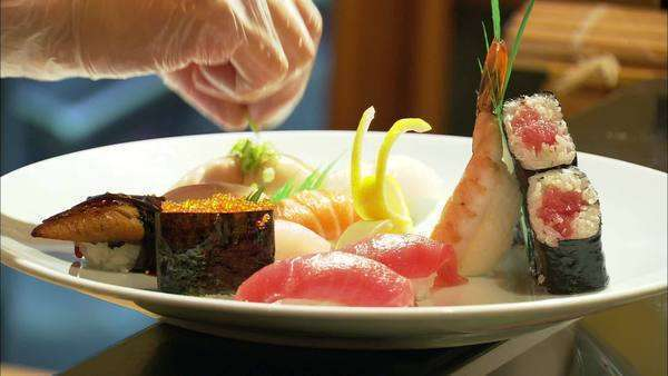 Close-up shot of a chef putting finishing touches on sushi platter Rights-managed stock video