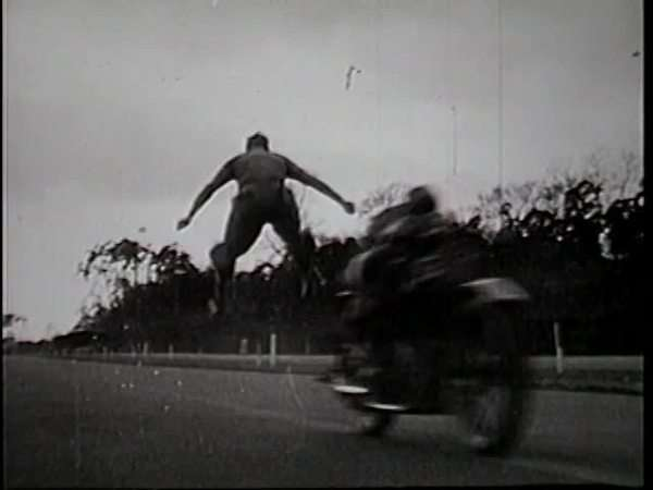 Hand-held shot of a man leaping over a moving motorcycle Rights-managed stock video
