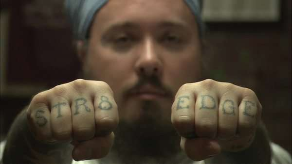 Close-up shot of a bearded man showing his tattooed fists Rights-managed stock video
