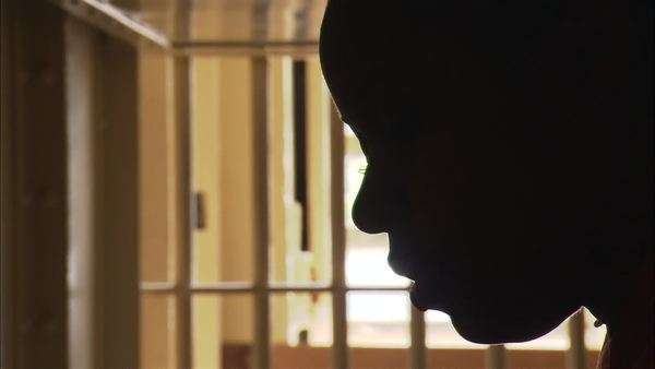 Static shot of a female prisoner reading aloud in her cell Rights-managed stock video