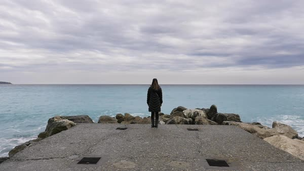 Wide shot of a woman standing on a pier in slow motion Royalty-free stock video