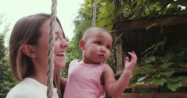 Mom pushing baby girl on swing Royalty-free stock video