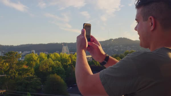 Medium shot of a young man taking photographs with his smartphone Royalty-free stock video